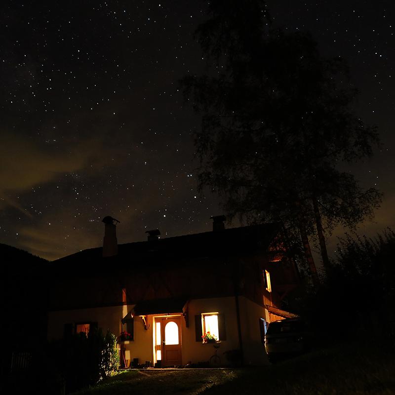 notte stellata e casa illuminata